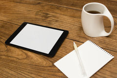 Digital tablet, notepad and coffee on table Stock Photos