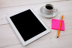 Digital tablet, notepad and cup of coffee on wooden background Royalty Free Stock Photos
