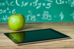 Digital tablet och äpple på skrivbordet royaltyfri bild