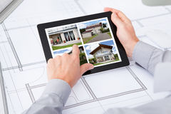 Digital Tablet Over Blueprint Browsing Pictures Of House. Architect Holding Digital Tablet Over Blueprint Browsing Pictures Of House Royalty Free Stock Image