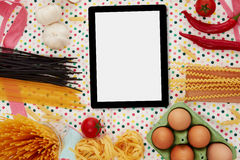 Digital tablet and pasta preparation Stock Photos