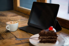 Digital tablet with pastry and coffee cup on table Stock Images