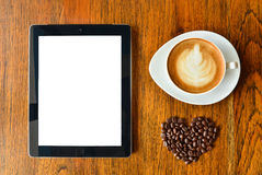 Digital tablet pc and a cup of coffee with heart shape Royalty Free Stock Photos