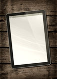 Digital tablet PC on a dark wood table Royalty Free Stock Image