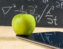 Digital tablet pc and green apple in front of blackboard on wood table. Concept of learn new technology Royalty Free Stock Photo