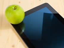 Digital tablet pc and green apple on wood table Stock Photo