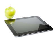 Digital tablet pc near green apple on white background Royalty Free Stock Images