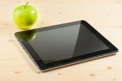 Digital tablet pc near green apple on wood table Stock Photo