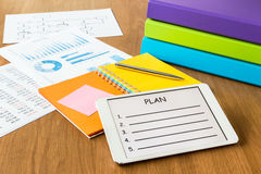 Digital tablet pc showing blank form of project planning. On a display screen, colorful diary book, binders and documents on workspace Royalty Free Stock Photo