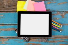 Digital tablet on pens, staple pins, color pencils and sticky notes. Against wooden plank Stock Images