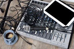 Digital tablet placed on a audio mixer with a coffee Stock Photo