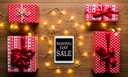 Digital tablet, presents and christmas lights, retro Boxing Day Sale concept. Desk view from above with digital tablet, presents and christmas lights, retro Royalty Free Stock Image