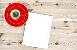Digital tablet and red cup of coffee on wooden table. Vintage st Stock Image