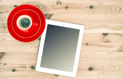 Digital tablet and red cup of coffee on wooden table. Vintage st Stock Photography
