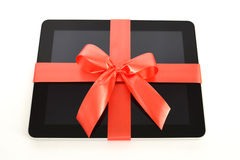 Digital tablet with red ribbon on white Royalty Free Stock Photography