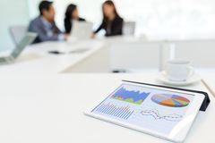 Digital tablet showing data chart in meeting room Royalty Free Stock Photo