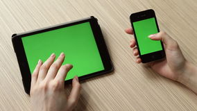 Digital tablet and smartphone with green screen on the table stock footage