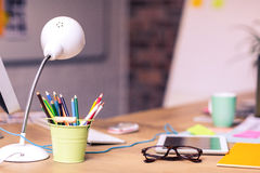 Digital tablet, spectacles and penholder on a table Stock Photos