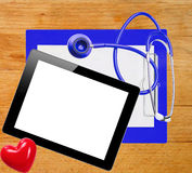 Digital tablet, stethoscope and blue clipboard over wooden Stock Image