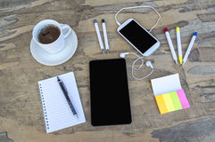 Digital tablet with sticky note paper, pens, smart phone, notebook and cup of coffee on old wooden desk. royalty free stock image
