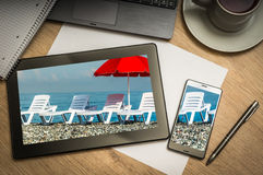 Digital tablet with sunbathing beds and red umbrella on screen Royalty Free Stock Image