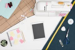 Digital tablet and tailoring items. Flat lay with digital tablet with blank screen, sewing machine, cutting sheet and other tailoring equipment on white royalty free stock photography
