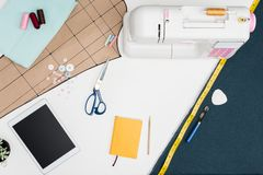 Digital tablet and tailoring items. Flat lay with digital tablet with blank screen, sewing machine, cutting sheet and other tailoring equipment on white stock image