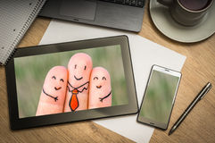 Digital tablet with three happy fingers on screen. Digital tablet on business table with three happy fingers on screen and mobile phone, paper, pen, laptop and Royalty Free Stock Photography