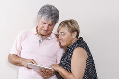 Digital tablet use by couple of senior people. Royalty Free Stock Images