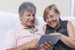 Digital tablet use by couple of senior people. Stock Photo