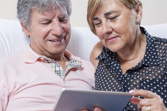 Digital tablet use by couple of senior people. Couple of senior people using digital tablet royalty free stock photography