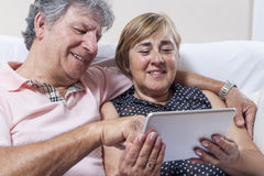 Digital tablet use by couple of senior people. Royalty Free Stock Image