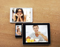 Digital tablets and smart phone with images on a desktop royalty free stock image