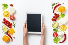 Digital-Tablette in den Frauenhänden und Kräuter und Gemüse lokalisiert auf weißem Hintergrund Kopieren Sie Platz lizenzfreie stockbilder