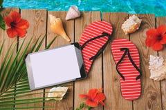 Digital-Tablette, Flipflops und Hibiscusblumen auf hölzernem Hintergrund Sommerferien-Ferienkonzept Ansicht von oben Stockfotos