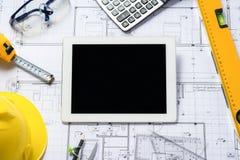 Digital-Tablette mit Architekturplanrollen und -werkzeugen Stockbilder