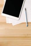 Digital-Tablette und -papier auf Holztisch Stockfoto