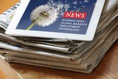 Digital-Tabletteninternet-Nachrichten auf Papierzeitung Stockfotos