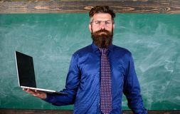 Digital technology education. Teacher bearded man with modern laptop chalkboard background. Online education. Modern. Technology education. Hipster teacher wear stock photos
