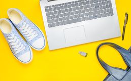 Digital technology and fashionable women's accessories on a yellow background: laptop, usb flash drive, bag, wallet, sneakers royalty free stock image