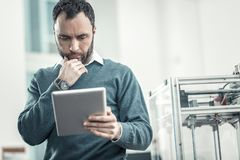 Serious thoughtful adult man using a tablet. Digital technology. Serious thoughtful man using a tablet while working in the office royalty free stock image