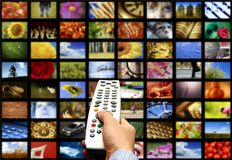 Digital television. Hand holding a remote control against a wall of multiple screens for digital television Stock Images