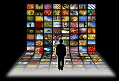 Digital television. Man standing in front of flat panels screens with images, concept for digital television Stock Photography