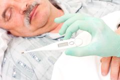 Digital thermometer. Temperature taken  by nurse of an elderly male patient Stock Photo