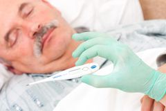 Digital thermometer. Temperature taken  by nurse of an elderly male patient Royalty Free Stock Photos