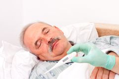 Digital thermometer. Temperature taken  by nurse of an elderly male patient Stock Photos