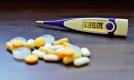Digital thermometer and pills Stock Photo