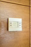 Digital thermostat panel on wooden wall Stock Image