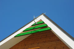 Digital TV aerial, antenna on rooftop of a modern house against blue sky Royalty Free Stock Image