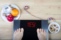 Digital våg med kvinnlig fot på dem och tecken` ja! ` som omges av sund mat arkivfoton
